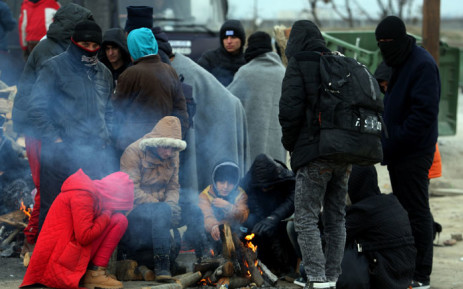 FILE: Migrants and refugees warm themselves by a fire as they wait to cross the border. Picture: AFP.