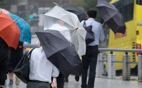 FILE: Pedestrians holding umbrellas walk in the rain in Tokyo on 8 August 2018. A powerful typhoon was churning towards Japan on August 8, prompting the weather agency to warn of heavy rain and strong winds and forcing airlines to cancel scores of flights. Picture: AFP