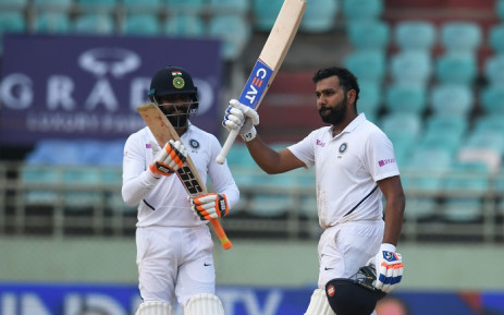 Indian cricketer Rohit Sharma (R) raises his bat after scoring a century (100 runs) during the fourth day's play of the first Test match between India and South Africa at the Dr. Y.S. Rajasekhara Reddy ACA-VDCA Cricket Stadium in Visakhapatnam on 5 October 2019. Picture: AFP