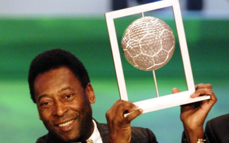 """Brazilian former soccer player Pele holds his Fifa grand prix of """"Footballer of the century"""" on 11 December 2000. Picture: AFP."""