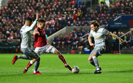 Bristol City's Jamie Paterson looks to find a way beyond Manchester United's Marcus Rojo and Daley Blind. Picture: @bcfctweets/Twitter