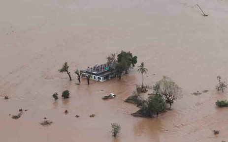 FILE: This handout picture taken and released on 18 March 2019 by the Mission Aviation Fellowship shows people on a roof surrounded by flooding in an area affected by Cyclone Idai in Beira. Picture: AFP