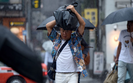 FILE: People walk under heavy rain in downtown Tokyo on 22 August 2016. A typhoon is on course for a direct hit on Tokyo, with nearly 400 flights grounded due to heavy rain and strong winds. Picture: AFP.