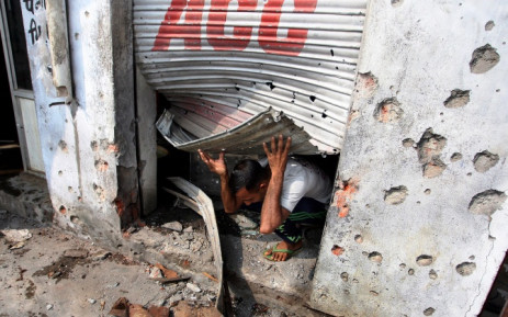 """"""" An Indian villager comes out of his shop, allegedly damaged by shelling from the Pakistani side of the disputed Kashmir border, at Arnia village, about 45 KM from Jammu, the winter capital of Kashmir, India, 7 October 2014. Picture: Jaipal Singh/EPA."""