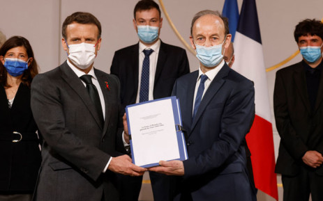 French President Emmanuel Macron (L) jointly holds a document along side historian Vincent Duclert, who heads the Rwandan commission at the Salle des Fete at the Elysee Palace in Paris on 26 March 2021. Picture: Ludovic Marin/AFP