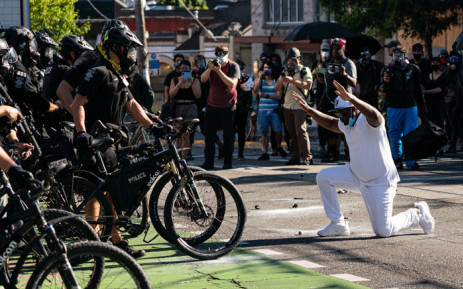 A demonstrator kneels in front of police during protests in Seattle on 25 July 2020 in Seattle, Washington. Police and demonstrators clash as protests continue in the city following reports that federal agents may have been sent to the city. Picture: AFP.