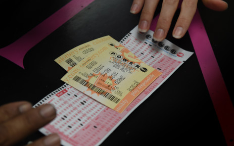FILE: A customer picks up her California Powerball lottery tickets at the famous Bluebird Liquor store which is considered to be a lucky retailer of tickets, in Hawthorne, California on 13 January, 2016. Picture: AFP.