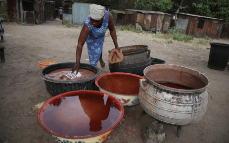 """A woman dips a bucket into a large bucket of """"burukutu"""", a locally brewed alcoholic beverage made from the fermented grains of sorghum and millet, in Makurdi, Nigeria, on December 15, 2019. Burukutu, the vinegary alcoholic beverage has been made here for generations from the fermented grains of sorghum and millet and consumed as a traditional alternative to beer. Picture: AFP"""