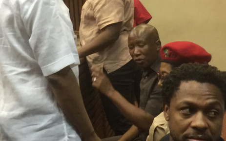 The EFF's Julius Malema (hand raised) and Mbuyiseni Ndlozi (foreground) appear in the Randburg Magistrates Court on 20 November 2019. Picture: Nthakoana Ngatane/EWN