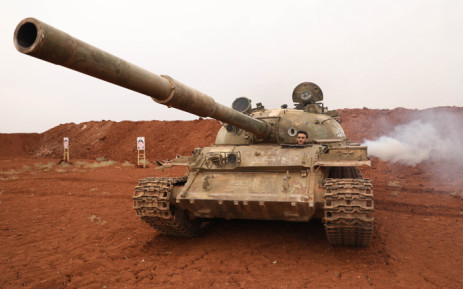 FILE: A Syrian rebel-fighter from the National Liberation Front (NLF) secures a tank, part of heavy weapons and equipment withdrawn on 8 October 2018 from a planned buffer zone around Idlib in one of the group's rear positions in a rebel-held area in the south-western Syrian province. Picture: AFP.