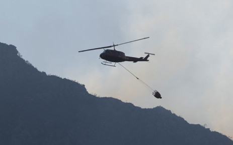 This picture taken in Cape Town on 18 April 2021 shows a fire-fighting helicopter picking up water from a reservoir to help extinguish a forest fire burning out of control on the foothills of Table Mountain, above the University of Cape Town. Picture: Rodger Bosch/AFP