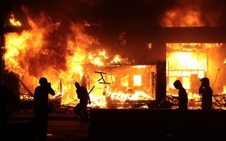 People stand near a burning building during protests sparked by the death of George Floyd while in police custody on 29 May 2020 in Minneapolis, Minnesota. Picture: AFP