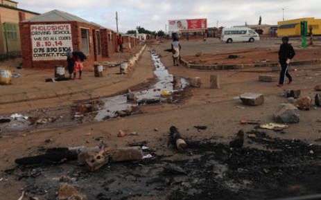 FILE: A woman walks across burnt tyres, rocks and sewage spill in Bekkersdal during service delivery protests in October 2013. Picture: Sebabatso Mosamo/EWN.