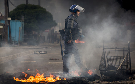FILE: A Public Order Police Officer walks passed a pile of burning debris used as a roadblock during riots in Masiphumelele in Cape Town. Picture: Thomas Holder/EWN