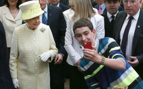 FILE: A boy takes a selfie with Queen Elizabeth II during a visit to Belfast, Northern Ireland. Picture: AFP.