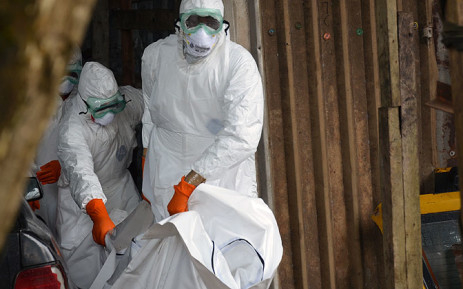Liberian Red Cross health workers wearing protective suits carry the body of a victim of the Ebola virus out of a garage on 10 September, 2014 in a district of Monrovia. Picture: AFP