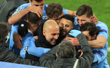 FILE: Manchester City players celebrate with manager Pep Guardiola during a UEFA Champions League match. Picture: Wolfgang Rattay/AFP