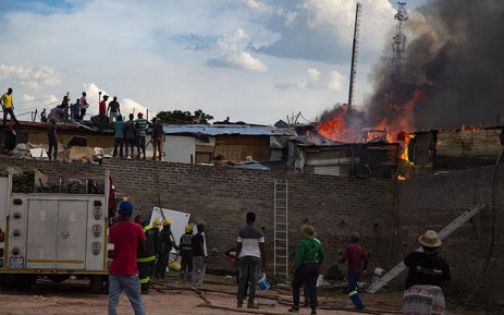 Residents work with firefighters to put out a fire that broke out at the Alexandra informal settlement on 6 December 2018. Picture: Kayleen Morgan/EWN