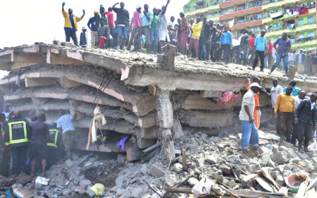 People stand on top of a collapsed six-storey building, as search and rescue continue in Nairobi, on 6 December 2019. Picture: AFP