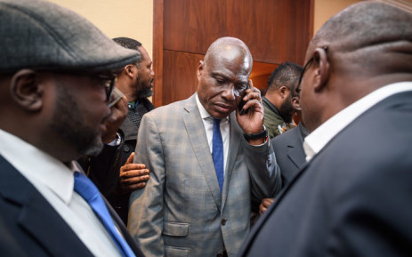 FILE: Democratic Republic of Congo joint opposition presidential candidate Martin Fayulu (C) speaks on his mobile phone following his designation on 11 November, 2018 in Geneva. Picture: AFP