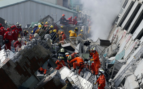 Rescuers help a survivor out of a collapsed building following a 6.4 magnitude earthquake that struck the area in Tainan City, Taiwan, 6 February 2016. Picture: EPA/RITCHIE B. TONGO.