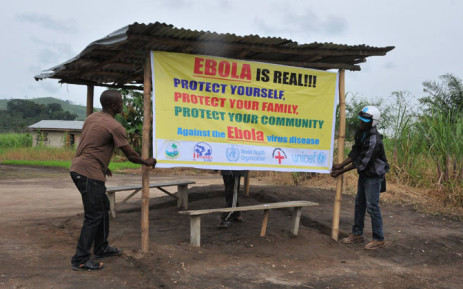 FILE: World Health Organisation volunteers putting up a banner warining people about the realness of the Ebola outbreak in West Africa. Picture: Official WHO Facebook page.