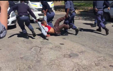A man is dragged into a police van after officers fired rubber bullets at protesting students at Rhodes University on 28 September 2016. Picture: Screebgrab.