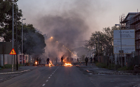 A protester taunts police as service delivery riots continued in Langa, Cape Town, where residents protesting against what they say is an unfair allocation of newly built houses in the township, closed Bhunga Avenue by burning tyres and littering the road with debris. Picture: Thomas Holder/EWN