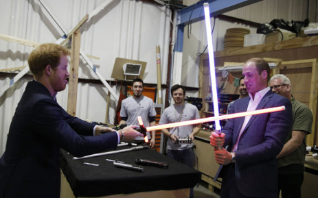 Britain's Prince Harry (L) and Prince William, Duke of Cambridge try out light sabres during a tour of the Star Wars sets at Pinewood studios in Iver Heath, west of London on 19 April 2016. Prince William and Prince Harry are touring Pinewood to visit the production workshops and meet the creative teams working behind the scenes on the Star Wars films. Picture: AFP/ADRIAN DENNIS