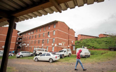 A resident passes the Russia, or R Block, of the Glebelands hostel, allegedly a haven for hitmen who operate throughout the province of KwaZulu-Natal in 2017 in Durban. Picture: AFP.