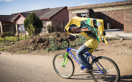 FILE: A young boy cycles holding an ANC poster. Picture: Thomas Holder/EWN.