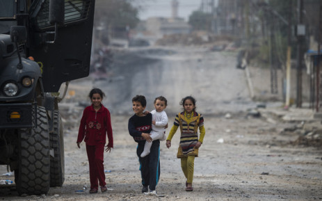 FILE: Children emerge from their houses to greet soldiers from the Iraqi Special Forces 2nd division during a lull in the fighting with IS fighters while pushing into the Aden neighbourhood in Mosul on 16 November, 2016. Picture: AFP.