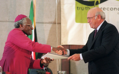 This file photo taken on 21 August 1996 shows former South African president FW de Klerk (R), handing over the party's submission to Archbishop Desmond Tutu, head of the Truth and Reconciliation Commission (TRC) during the National Party's submission before the TRC in Cape Town. Picture: Anna Zieminski/AFP.