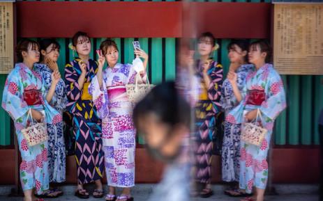 Women wearing yukatas, a traditional Japanese summer outfit, pose for selfies with their mobile phones at Sensoji temple in Tokyo on 22 July 2021, on the eve of the start of the Tokyo 2020 Olympic Games. Picture: Philip Fong/AFP