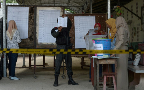 A security personnel and electoral officials count votes at a polling station in Narathiwat on March 24, 2019 after polls closed in Thailand's general election. Picture: AFP.