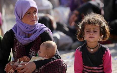 FILE: A Yazidi Iraqi woman sits with her children at the Bajid Kandala camp near the Tigris River, in Kurdistan's western Dohuk province, where they took refuge after fleeing advances by Islamic State jihadists in Iraq on 13 August, 2014. Picture: AFP.
