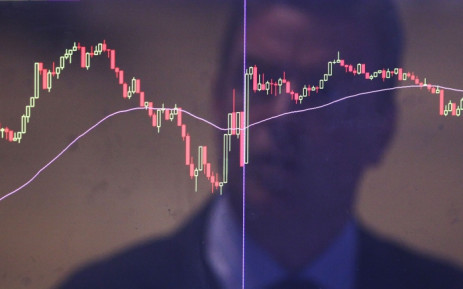 A stock trader reflected in a market screen. Picture: AFP.