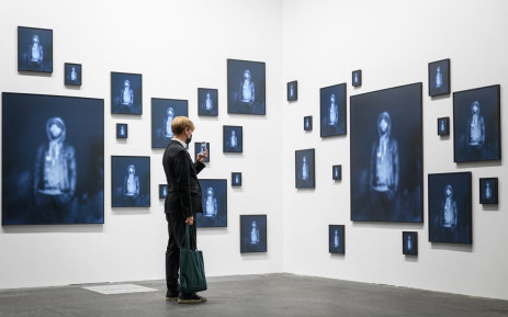 """A visitor takes a photo with his mobile phone of """"Repeating the Obvious, 2019"""", an artwork by US artist Carrie Mae Weems, exhibited in the Unlimited sector of Art Basel. Picture: AFP"""