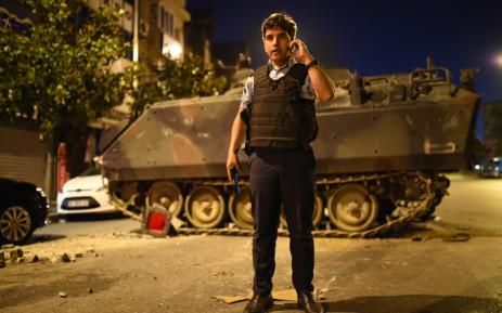 A Turkish police officer talks on a phone during clashes in Istanbul on 16 July 2016. Picture: AFP.