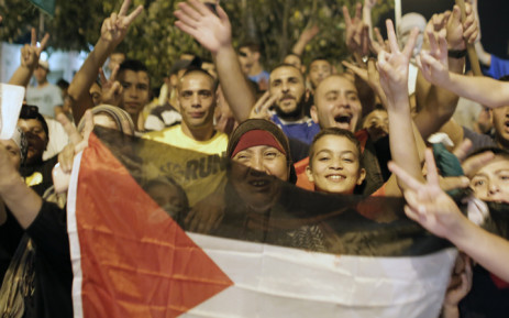 FILE: Palestinians flash the sign of victory wave a national flag as they celebrate in the streets in East Jerusalem the long-term truce agreed between Israel and the Palestinians on August 26, 2014