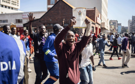 A protester holds a copy of the Constitution of Zimbabwe during a demonstration and clashes with the police in Harare on 16 August 2019. Picture: AFP