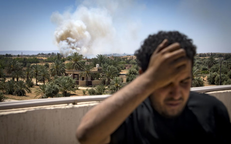 A fighter loyal to the internationally-recognised Government of National Accord (GNA) stands on a rooftop as smoke rises in the distance during clashes with forces loyal to strongman Khalifa Haftar, in Espiaa, about 40 kilometres south of the Libyan capital Tripoli on 29 April 2019. Picture: AFP