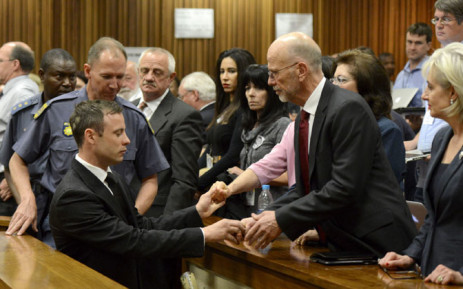 Oscar Pistorius holds the hands of family members as he is taken down to the holding cells after being sentenced to five years imprisonment for the culpable homicide death of his girlfriend Reeva Steenkamp. Picture: Pool.