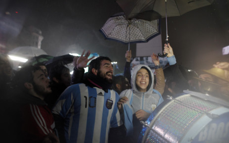 Fans of Argentine football star Lionel Messi rally under the rain asking for his return to the national team at the Obelisco in Buenos Aires on 2 July, 2016. Picture: AFP.