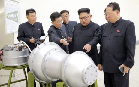 FILE: This undated picture released by North Korea's official Korean Central News Agency (KCNA) on 3 September 2017 shows North Korean leader Kim Jong-Un (C) looking at a metal casing with two bulges at an undisclosed location. Picture: AFP.