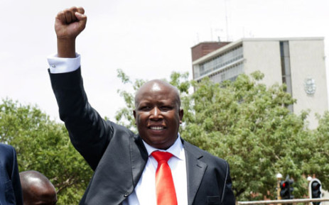 Julius Malema greets supporters outside the Polokwane Regional Court on November 30, 2012. Picture: AFP.