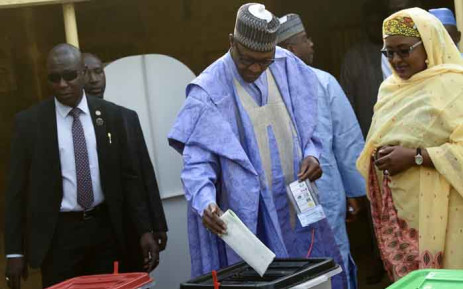 Candidate of the All Progressives Congress (APC) and incumbent President Muhammadu Buhari (C), flanked by his wife Aisha Buhari (R), casts his vote at a polling station in his native hometown Daura in Katsina State, northwest Nigeria, on 23 February 2019. Nigerians began voting for a new president on 23 February after a week-long delay that has raised political tempers, sparked conspiracy claims and stoked fears of violence. Picture: AFP