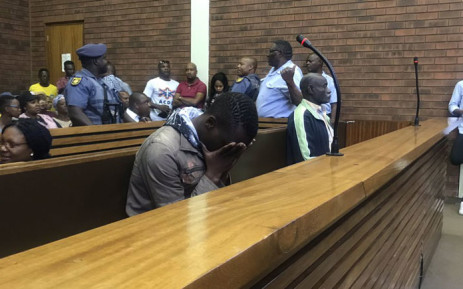 Ernest Mabaso (head in hands) and Fita Khupe (right) appear in Lenasia Magistrates Court on 12 November 2018 for allegedly killing seven people in Vlakfontein. Picture: Bonga Dlulane/EWN