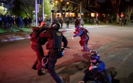 Portland police officers tackle demonstrators after a riot was declared during a protest against the killing of Daunte Wright on 12 April 2021 in Portland, Oregon. Picture: AFP
