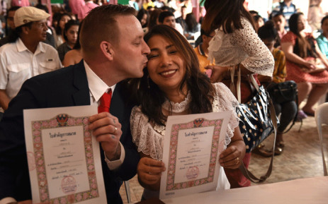A Thai woman and a British man hold up their marriage certificates on Valentine's Day at the central post office in the Bang Rak, or 'Love Village', district in Bangkok on 14 February 2018. Picture: AFP